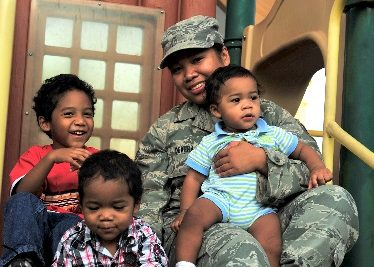 female airman in uniform sitting on steps with her three toddler children