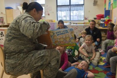 children and adults sitting on floor in a childcare facility room while a female airman reads from a picture book