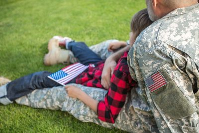 Child sitting on military father's lap on grass