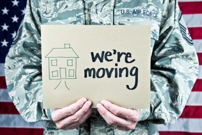 """US flag in background, torso of male military service member holding sign that reads """"We're moving"""" and an image of a house"""