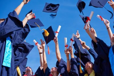 people dressed in dark blue academic graduation gowns with hands extended into the air and mortarboard caps flying in the air