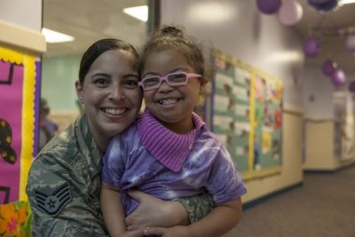 Mom in Air Force Uniform hugging daughter during April, the month of the Military Child.