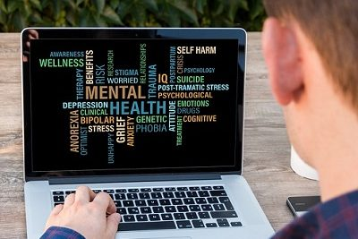 teen with laptop viewing mental health word cloud