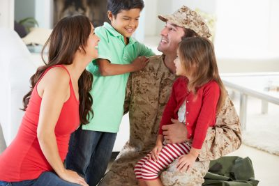 Man in military uniform kneeling with one arm around his son who is wearing a green polo shirt, the other arm around his daughter who is sitting on his knee, and in front of him is his wife kneeling as well. All family members are smiling.