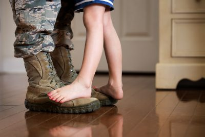 Child's feet standing on boots of Airmen parent