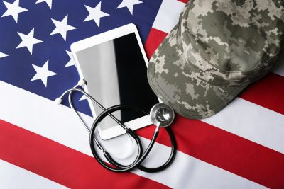 A camouflage cap, stethoscope, and computer tablet lay on top of a United States flag