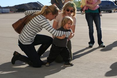 image of a toddler on an airfield crying; two distraught women kneel next to him trying to keep him from running forward
