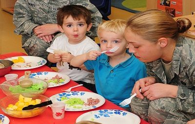 Photo of 2 male toddlers photographed sitting at a child-sized table, caught mid-bite; next to one of the toddlers is a female Air Force member with another in the background. There are paper plates with fluffy green colored-food and bits of what look like ham in front of the toddlers. The caption reads: The Child Development Center staff celebrates Dr. Seuss's birthday by hosting a green eggs and ham breakfast-Beale Air Force Base