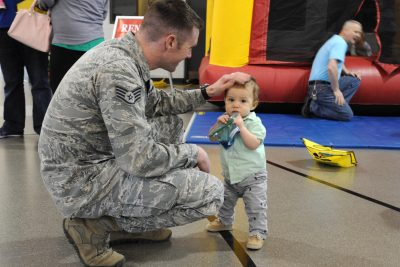 Man in Air Force uniform squats and is patting the head of a standing boy less than a year old.