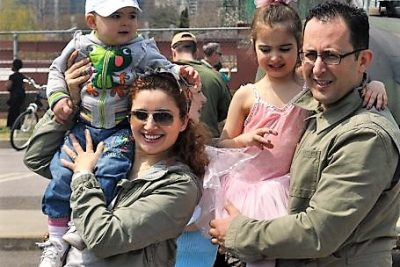 a couple hold their children on their shoulders-mom is carrying a boy toddler, and dad carries an elementary aged girl dressed as a ballet dancer. They are in a parking lot, and some sort of camouflaged vehicle is in the background.