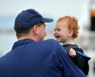 Coast Guard dad holding laughing toddler