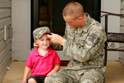 Military dad on front porch of house sitting next to his toddler daughter wearing his cap