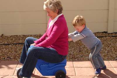little boy pushing grandmother on plastic tricycle