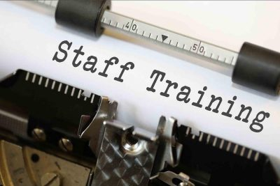 "image of paper in a typewriter with the words ""staff training"" typed in"