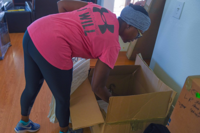 image of African-American woman bending over a packing box while holding sheets of packing paper.