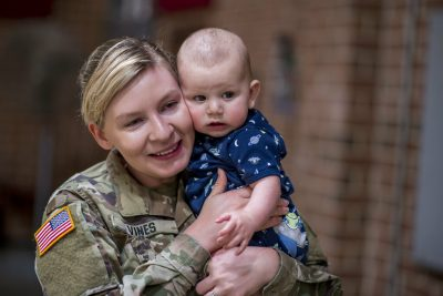 Female Army National Guard service member leaning her head against her baby son's head while she holds him. Her eyes are wet.