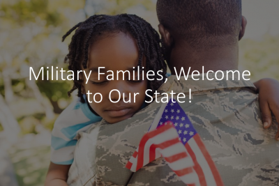 "A male military service member carries a small girl against his shoulder. The girl's eyes are closed as though sleeping. She carries a small American flag in her hand. Superimposed text over the image reads"" Military Families, Welcome to Our State!"